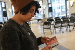 A volunteer shows brochures made by artists while explaining artworks. (Xiaozhang (Shaw) Wan/MEDILL)