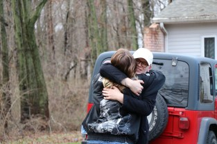 Beth Braun embraces her friend and neighbor Mikey Reid, 23, upon arriving at his home to collect soil. (Becky Dernbach/MEDILL)