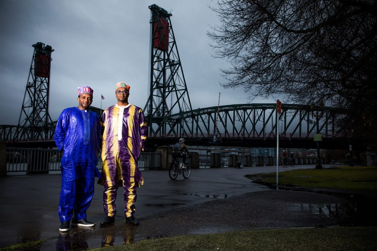 Photograph of brothers Ibrahima and Abdoulaye Barry in front of a bridge on the Willamette River in Portland, Oregon