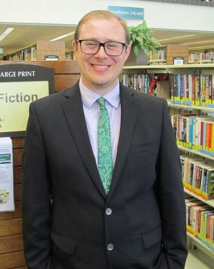 photo of David Kelsey in a suit with a green tie