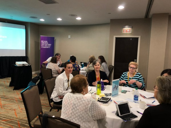 photo of the room at the preconference. Attendees are talking amongst themselves