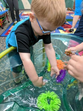 Child interacting with toys in a tub full of water