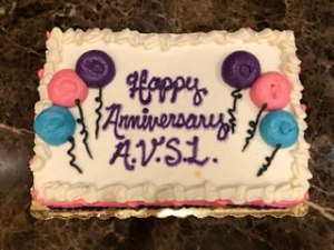 cake decorated with white icing and balloons signed happy anniversary avsl
