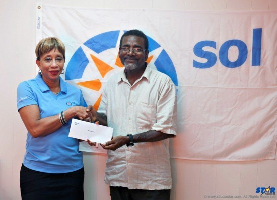 Sol St. Lucia's GM  Eugenie Dalson congratulates winner Bill Mortley.