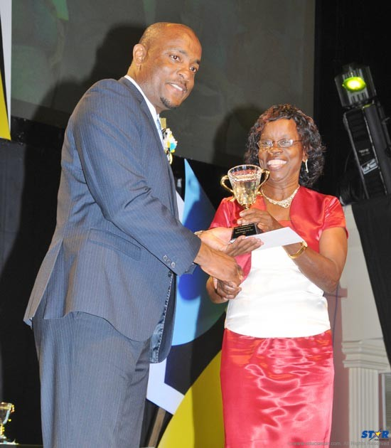 Anne Marie Spencer received the Sportswoman of the Year award from Minister of Sports Shawn Edward on behalf of daughter Levern.