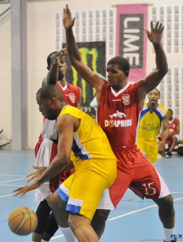Marcian Calderon (VBCC Warlords) closely guarded by Desmond Vidal (Dennery Dolphins) in a semi-final game.