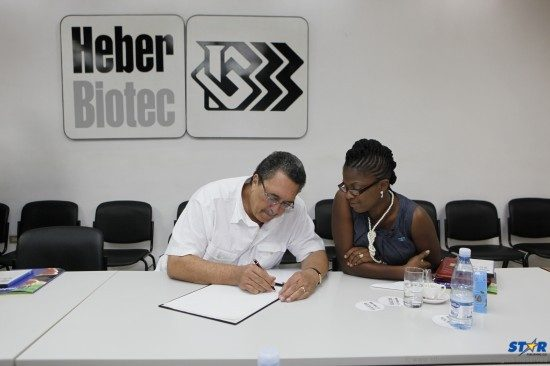 Prime Minister Kenny Anthony, under the watchful eye of his press secretary Jadia Jn Pierre Emmanuel, signs the guest book at the Biomedical Facility in Havana during a recent visit to Cuba.