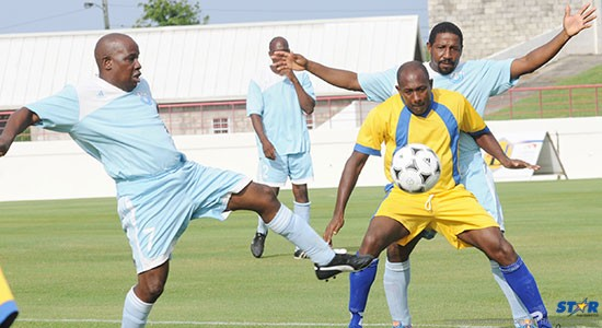 Gilroy Hall (l) of Lancers FC and and a teammate try to keep this Laborie in check.