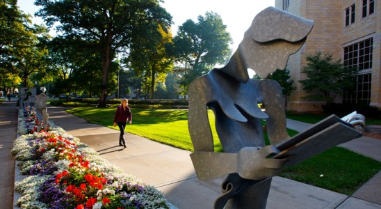 """A student walks by the """"In the Beginning"""" sculpture on south campus."""