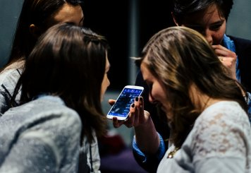 Members of Cadenza listen to a song sample on a phone during a practice session.