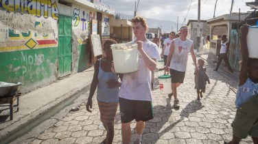 St. Thomas students Danny Burke, left, and Willie Falk, right, help Haitians - often restavecs (slave children) - carry clean water from the truck back to their homes.