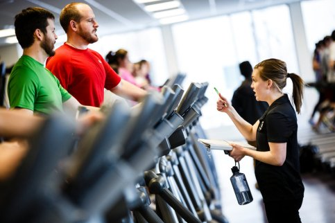 Sophie Gottsman talks with seminarians Daniel Button (green shirt) and T.J. McKenzie as they work out on elliptical machines.