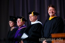 Commencement speaker Archie Black, CEO of SPS Commerce, right, smiles during the graduate business commencement ceremony May 23, 2015 in the Anderson Athletic and Recreation Complex Field House.