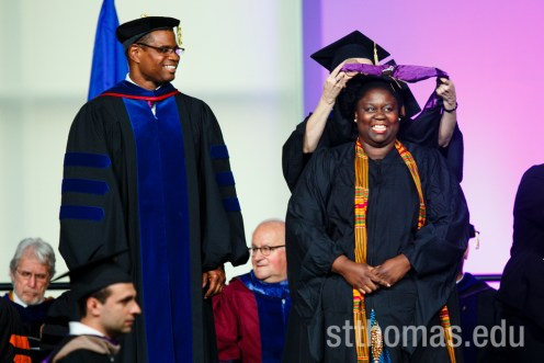A graduate student smiles while receiving her hood during the graduate business commencement ceremony May 23, 2015 in the Anderson Athletic and Recreation Complex Field House.