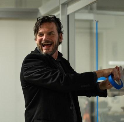 Professor Johnson creates a cross in blue tape.