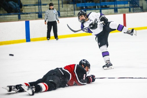 Jordan Lovick fires a shot on goal over a diving defender during a men's hockey game against the University of Wisconsin-Whitewater.