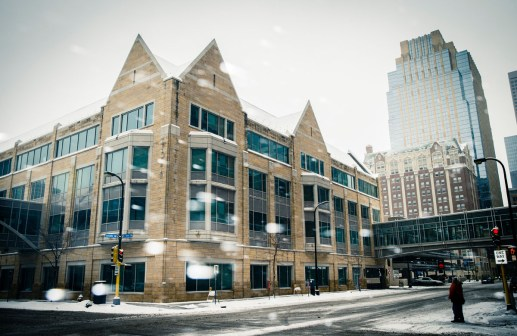 Snow falls in front of Opus Hall.