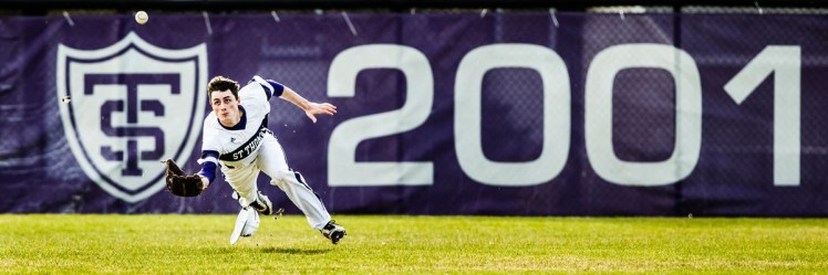 Jimmy Dolan dives for a fly ball in the outfield.