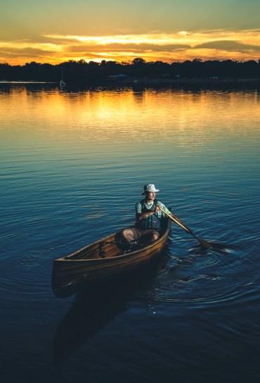 Communication and journalism professor Mark Neuzil poses in his handmade wooden canoe.