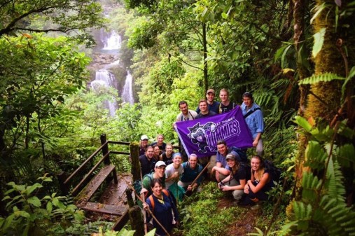 """First place, Tommies Abroad: Nick Hable, Costa Rica. """"Hidden Oasis in the Costa Rican Jungle: This photo shows our biology study abroad group holding the St. Thomas flag with a pristine waterfall in the background. This was in the middle of the Costa Rican jungle, next to Rara Avis, and we came across this after our four-hour hike into the jungle. This remote location is virtually untouched by humans, has a livelihood of animals and indigenous plants, and has little access to water and electricity. This location showed how simple life can be and it also changed our perspectives on how we view society in the United States."""""""