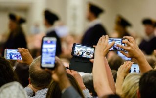 Family members take cell phone photos as graduates process in during the School of Law Commencement ceremony May 13, 2017 at the Minneapolis Hilton.