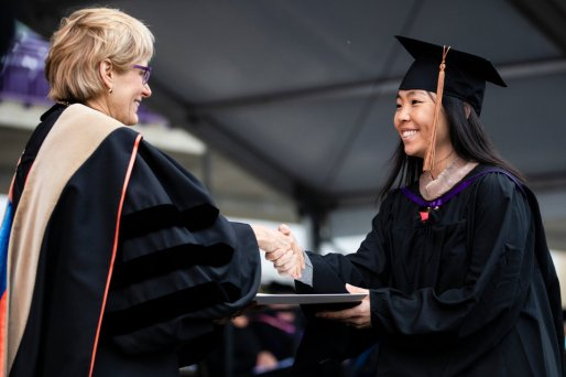 A student shakes hands with President Julie Sullivan as she receives her degree during the 2018 Graduate Commencement ceremony in O'Shaughnessy Stadium on May 18, 2018 in St. Paul.
