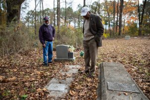 Steve Bullock, right, and his nephew Charles Bullock, 75, left, stand over the grave of Steve's father, William Henry Bullock at the cemetery in his hometown of Enfield, North Carolina on November 23, 2018. Steve Bullock was photographed for a feature story in St. Thomas Magazine.