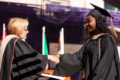 President Julie Sullivan hands a diploma to a graduate during the 2019 Graduate Commencement Ceremony in O'Shaughnessy Stadium on May 25, 2019 in St. Paul.
