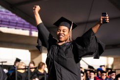 A student raises her arms in celebration as she walks across stage during the 2019 Graduate Commencement Ceremony in O'Shaughnessy Stadium on May 25, 2019 in St. Paul.