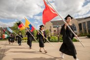 International students carry flags during the 2019 Graduate Commencement Ceremony in O'Shaughnessy Stadium on May 25, 2019 in St. Paul.