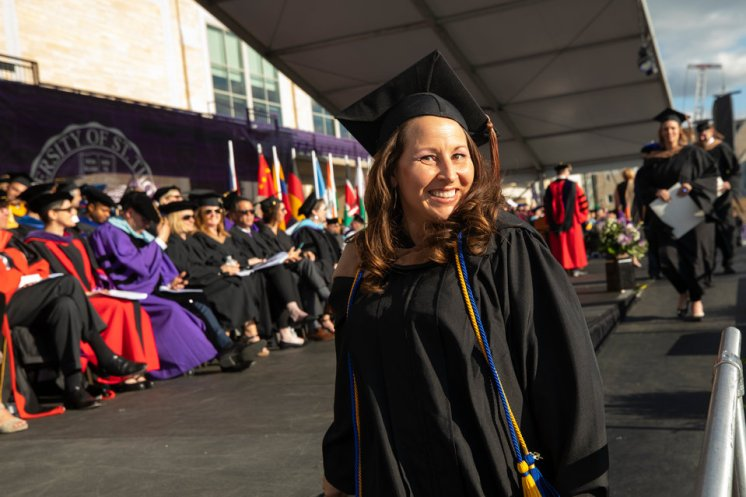 Melissa Palank, associate director of alumni events and operations, smiles after walking across the stage during the 2019 Graduate Commencement Ceremony in O'Shaughnessy Stadium on May 25, 2019 in St. Paul.