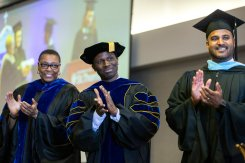 Administrators (l-r) Buffy Smith, Doug Thompson and Alvin Abraham applaud the Dougherty Family College graduates.