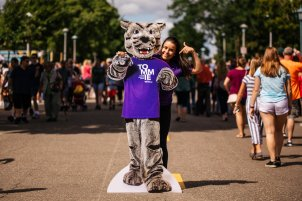 St. Thomas student Olivia Litecky poses with a Tommie cutout at the Minnesota State Fair