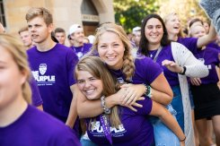 A student carries a friend on her back during the annual March through the Arches to celebrate the start of the school year and the arrival of a new class of freshmen on campus on September 3, 2019, in St. Paul.