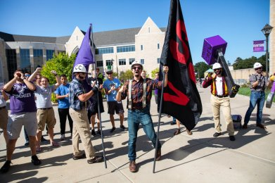 """Members of """"Caruso's Crew"""" celebrate during the annual March through the Arches to celebrate the start of the school year and the arrival of a new class of freshmen on campus on September 3, 2019, in St. Paul."""