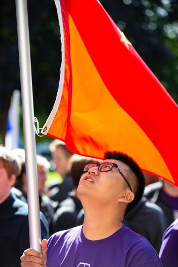 An international student looks up at his flag during the annual March through the Arches to celebrate the start of the school year and the arrival of a new class of freshmen on campus on September 3, 2019, in St. Paul.