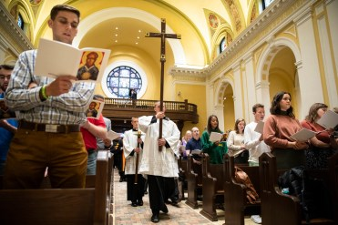 Students carry the cross during the Opening Mass Sept. 5, 2019 in the newly renovated interior of the Chapel of St. Thomas Aquinas.
