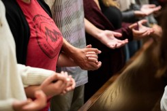 Students hold hands in prayer during the Opening Mass Sept. 5, 2019 in the newly renovated interior of the Chapel of St. Thomas Aquinas.