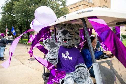 Tommie waves from a cart during the homecoming parade. (Liam Doyle/University of St. Thomas)
