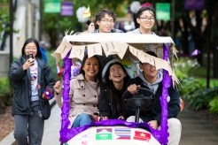 Students drive a golf cart during the homecoming parade. (Liam Doyle/University of St. Thomas)