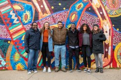 College of Arts and Sciences faculty and students participating in the SOLV initiative stand in front of the Braided, a mural that is part of the Midway Murals project, in St. Paul. Mark Brown/University of St. Thomas