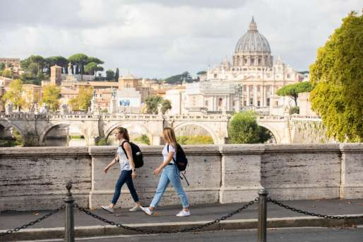 Students walk together to class from the Bernardi campus building in Rome, Italy with St. Peter's Basilica visible in the background. Liam James Doyle/University of St. Thomas