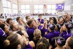 The men's and women's swimming teams gather around head coach Scott Blanchard for a group cheer. Liam James Doyle/University of St. Thomas