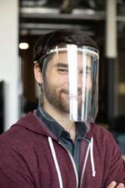 Isaac Fennewald pulls face shield headbands out of a dissolving wash.