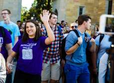 A student waves to the Facebook live camera during the March Through the Arches event September 8, 2016.