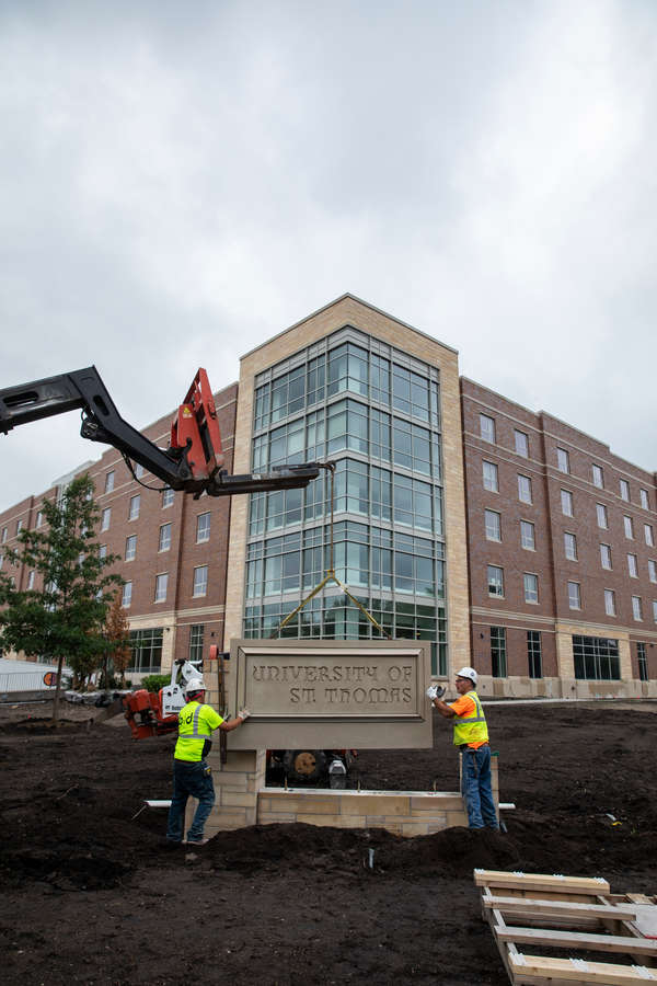 A crew for B&D Masonry installs the new sign in front of Tommie North Residence Hall.