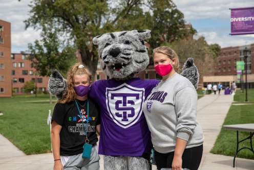 Tommie poses with students on the upper quad.