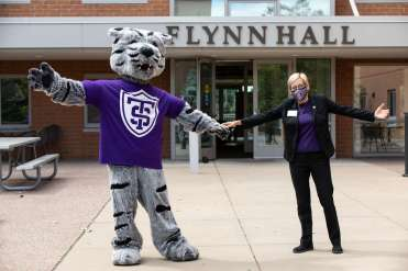 President Julie Sullivan poses for a photo with Tommie in front of Flynn Hall on Labor Day weekend.