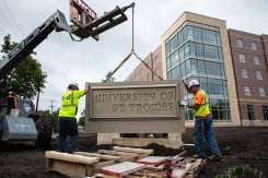 A construction crew installs a new University of St. Thomas monument sign at the corner of Cleveland and Selby. Mark Brown/University of St. Thomas