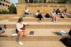 Students sit on the steps of the O'Shaughness-Frey Library during a communications class. Liam James Doyle/University of St. Thomas